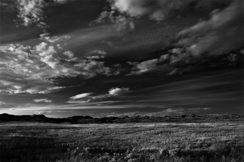 A wide-angle photograph of Grasslands National Park, rendered in greyscale